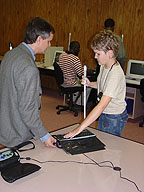 A blind ibtc consultant explains how to use a notetaker to a blind visitor.