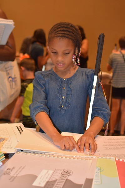 A young girl with a white cane reads from a Braille book.