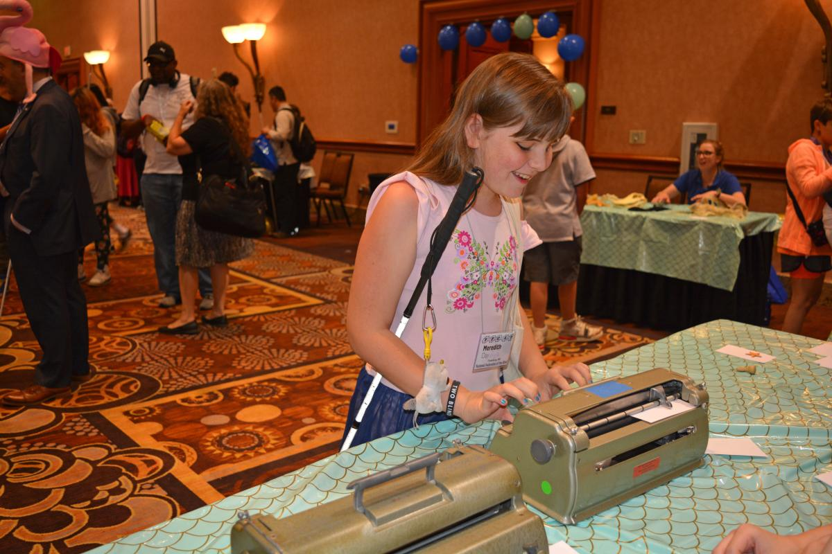 A young girl uses a Perkins Brailler at the Action Fund carnival celebration at the NFB National Convention.